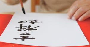 Escribiendo caligrafía china con el significado de la frase deséele las buenas FO Imagenes de archivo
