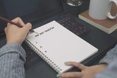Escribiendo la resolución del Año Nuevo enumere en metas del principio del notecook imagenes de archivo