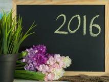 2016 escribieron en la pizarra decorativa con la flor artificial y g Imagenes de archivo