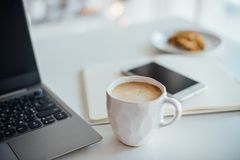Escritório branco moderno, copo feito a mão do desenhista com café, smartpho imagem de stock royalty free