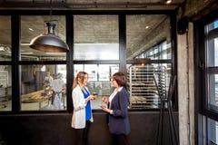 Escritório da padaria com as mulheres de negócio que falam junto fotografia de stock