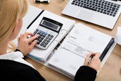 Escritório de Calculating Invoice In da mulher de negócios imagens de stock
