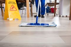 Escritório de Cleaning Floor In do guarda de serviço fotografia de stock