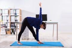 Escritório de Doing Workout In da mulher de negócios foto de stock