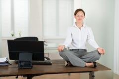 Escritório de Doing Yoga In da mulher de negócios foto de stock royalty free
