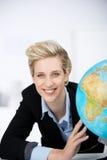 Escritório de sorriso de With Globe In da mulher de negócios foto de stock royalty free