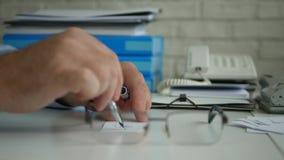 Escritório interior da imagem do close up do homem de negócios que assina o documento financeiro usando uma pena vídeos de arquivo