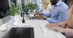 Escritório para negócios aberto com os membros do pessoal ocupados que datilografam em computadores, equipe da raça da mistura do filme