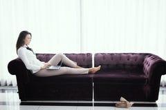 Escrit?rio domicili?rio Mulher bonita nova bem sucedida que senta-se em um sof? na sala de visitas e que usa o port?til fotografia de stock royalty free