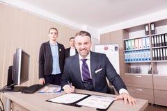 Escrita adulta do homem de negócios no dobrador com papper e seu colleagu Fotos de Stock Royalty Free