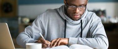 Escrita africana do estudo do estudante da foto horizontal usando o livro e o computador fotos de stock royalty free