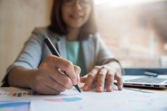 Escrita asiática da mulher de negócio no papel fotografia de stock