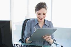 Escrita atrativa satisfeita da mulher de negócios na prancheta que senta-se em sua mesa Imagens de Stock Royalty Free