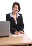 Escrita bonita da mulher de negócio na mesa de escritório Fotografia de Stock Royalty Free