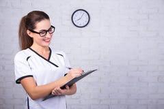 Escrita bonita nova do doutor da mulher algo na prancheta sobre Fotografia de Stock Royalty Free
