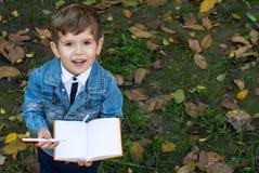 Escrita bonito da criança no caderno usando a pena e o sorriso Quatro anos de criança idosa que senta-se na grama imagem de stock royalty free