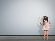 Escrita com a escova de pintura na parede vazia, vista traseira da criança fotografia de stock royalty free