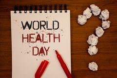 Escrita conceptual da mão que mostra o dia de saúde de mundo A foto do negócio que apresenta a data especial para atividades saud fotos de stock royalty free