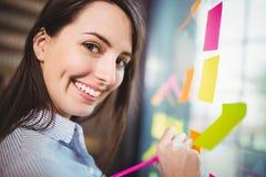 A escrita criativa da mulher de negócios em notas pegajosas colou ao vidro Imagens de Stock