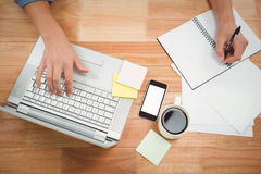 Escrita criativa do homem de negócios no livro espiral usando o portátil Imagem de Stock Royalty Free
