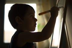 Escrita da criança em um quadro-negro foto de stock royalty free