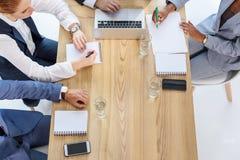 Escrita da equipe do negócio nos blocos de notas durante a reunião fotografia de stock royalty free