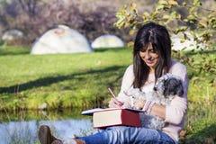 Escrita da jovem mulher com seu cão em um parque do outono Foto de Stock Royalty Free