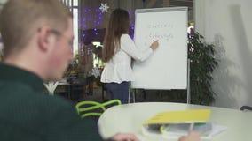 Escrita da jovem mulher na estratégia da placa do negócio do trabalho, explicando suas ideias ao colega masculino no escritório H filme