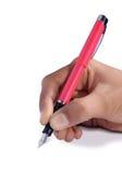 Escrita da mão com a pena no Livro Branco Imagens de Stock