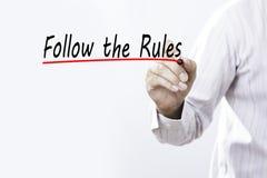 A escrita da mão do homem de negócios segue as regras com o marcador vermelho no tra Foto de Stock