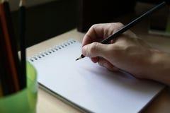Escrita da mão do homem no bloco de desenho fotografia de stock