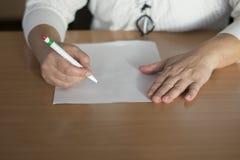 Escrita da mão do ` s da mulher do close up no papel Imagens de Stock Royalty Free