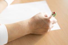 Escrita da mão do ` s da mulher do close up no papel Fotografia de Stock Royalty Free