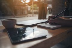 escrita da mão do ` s da mulher em um caderno vazio com o copo do portátil, da tabuleta e de café no fundo de madeira da tabela Imagem de Stock