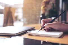 escrita da mão do ` s da mulher em um caderno vazio com o copo do portátil, da tabuleta e de café no fundo de madeira da tabela Foto de Stock