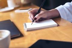 escrita da mão do ` s da mulher em um caderno vazio com o copo do portátil, da tabuleta e de café no fundo de madeira da tabela Imagem de Stock Royalty Free
