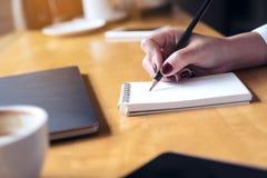 escrita da mão do ` s da mulher em um caderno vazio com o copo do portátil, da tabuleta e de café no fundo de madeira da tabela Imagens de Stock Royalty Free