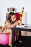 Escrita da menina com um lápis gigante Foto de Stock Royalty Free