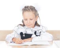 Escrita da menina da escola no caderno Foto de Stock