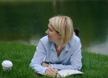 Escrita da moça em seu caderno no parque Imagens de Stock