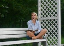 Escrita da moça em seu caderno no parque no banco Foto de Stock Royalty Free
