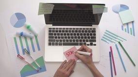 A escrita da mulher COMEÇA ACIMA em notas pegajosas Desktop do negócio com diagrama filme