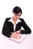 Escrita da mulher de negócio em sua mesa Imagens de Stock