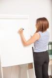 Escrita da mulher de negócios em uma placa da aleta Imagens de Stock Royalty Free