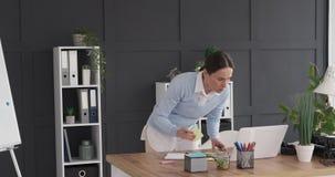 Escrita da mulher de negócios na nota adesiva e colagem no whiteboard video estoque