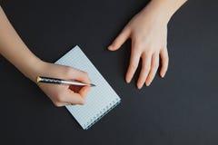 Escrita da mulher no bloco de notas na tabela preta imagens de stock royalty free