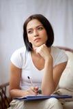 Escrita da mulher no bloco de notas para fazer em casa a lista Fotografia de Stock Royalty Free
