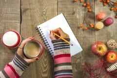 Escrita da mulher no caderno branco que guarda o café na garrafa térmica em rus Fotografia de Stock