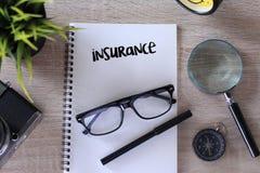 Escrita da palavra do seguro no caderno na tabela de madeira Imagens de Stock Royalty Free