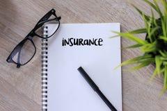 Escrita da palavra do seguro no caderno na tabela de madeira Fotografia de Stock Royalty Free